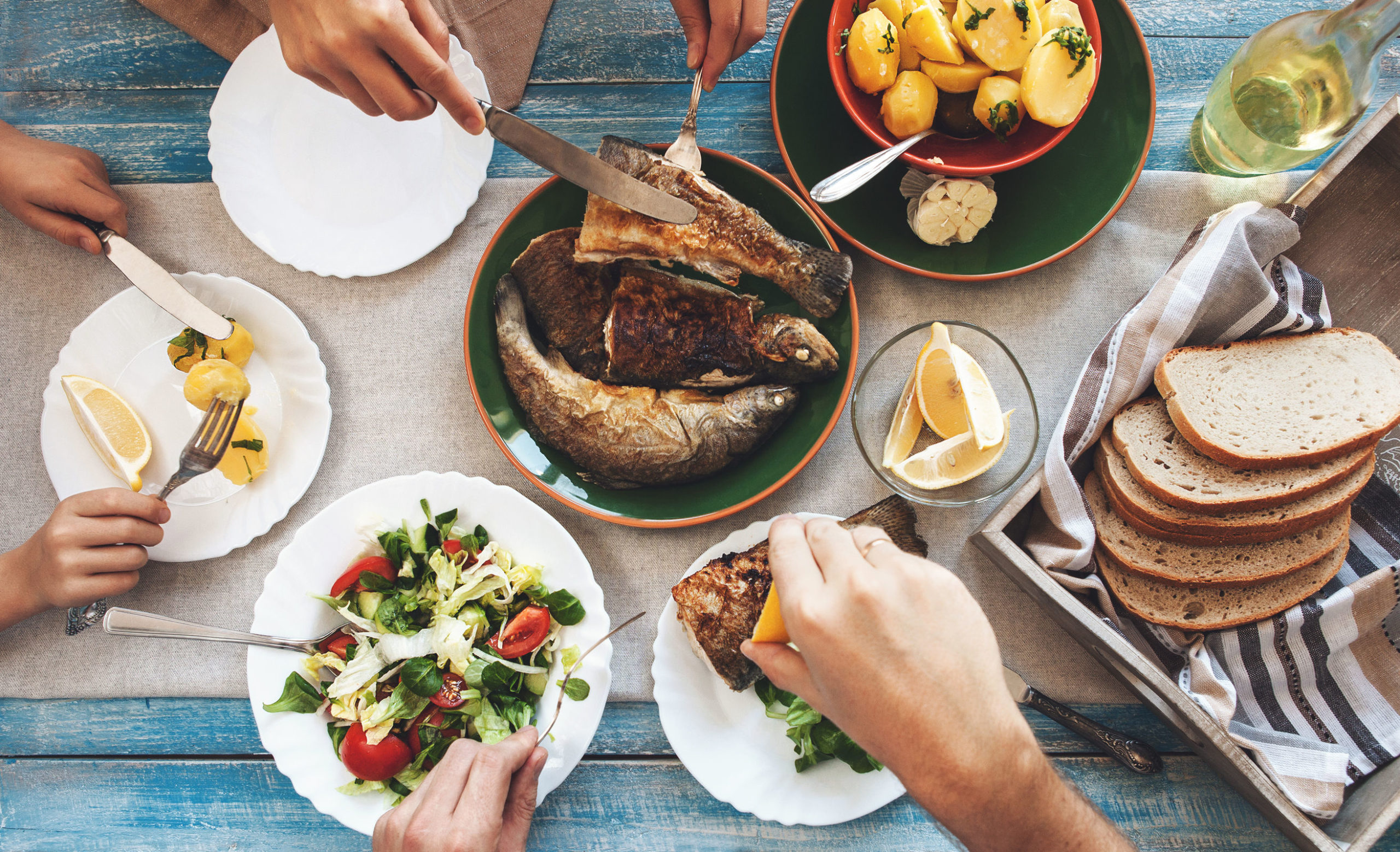 people eating fish and salad around a table